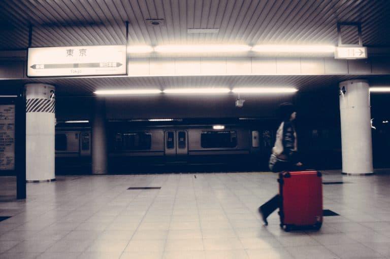 Person rollt Koffer durch U-Bahn Station