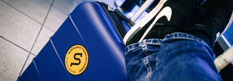 Reisender lagert Füße auf seinem Koffer