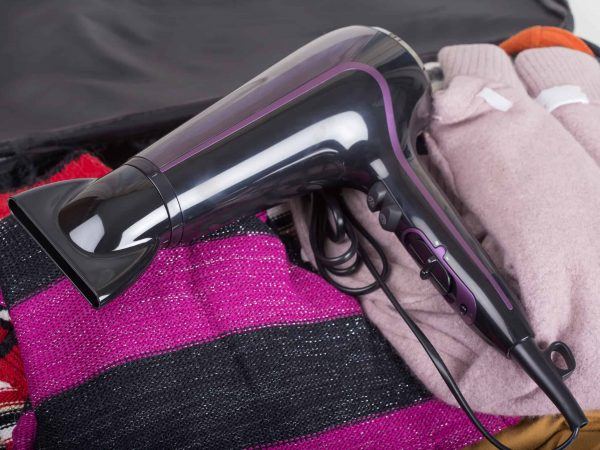 Modern hair dryer on travel bag with clothes