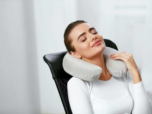 Travel Pillow. Young Woman With Pillow On Neck Sitting In Chair. High Resolution.