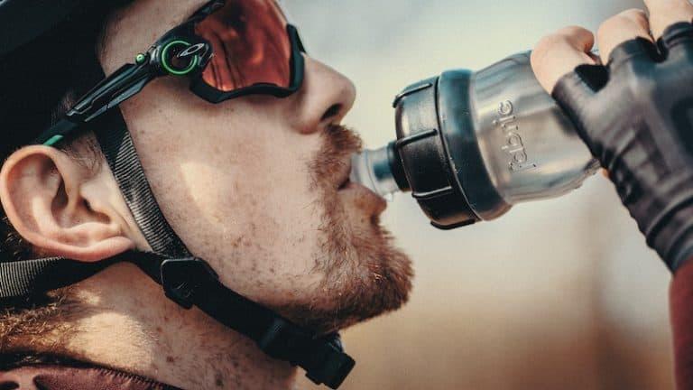 Ein Radfahrer trinkt aus einer Flasche