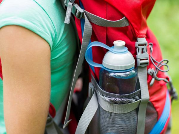 travel, tourism, hike and people concept – close up of woman with water bottle in backpack pocket